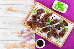 Hot sticky ribs on parchment paper on chopping board Stock Photo
