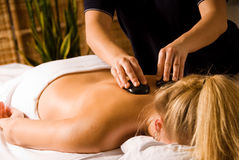 Hot stone. Therapist giving a hot stone massage to woman stock photos
