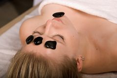 Hot Stone Facial Massage. Woman in spa receives hot stone facial treatment. selective focus royalty free stock images