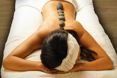 HOT STONE MASSAGE. Detail of young Asian lady with rocks on her back, receiving a hot stone massage Royalty Free Stock Photography