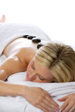 Hot Stone Massage. A woman gets a hot stone massage at a day spa royalty free stock image