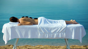 Hot stone massage. Girl on massage table with hot stones on her back Stock Photo