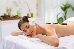 Hot stone massage. Attractive woman getting hot stone massage Stock Photography