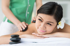 Hot stone massage. Close-up of a serene woman having hot stone spa massage on the foreground royalty free stock photos
