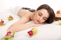 Hot stone massage in the day spa Stock Images