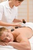 Hot stone massage - man at spa Stock Photography