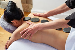 Hot stone massage in woman back physiotherapist Royalty Free Stock Images