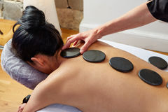 Hot stone massage in woman back physiotherapist Royalty Free Stock Photography