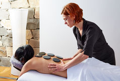 Hot stone massage in woman back physiotherapist Stock Photo