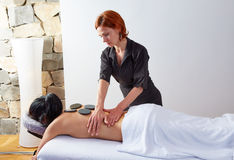 Hot stone massage in woman back physiotherapist Stock Photos