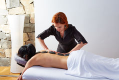 Hot stone massage in woman back physiotherapist Royalty Free Stock Image