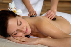 Hot stone massage woman enjoy spa treatment. Woman with flower at spa having hot stone back treatment royalty free stock photography