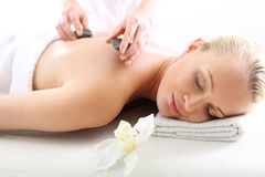 Hot stone massage, a woman in spa salon Stock Images