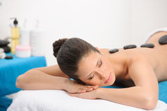 Hot stone massage of a young woman Royalty Free Stock Photos