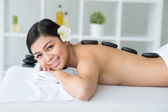 Hot stone spa massage. Portrait of a lady having hot stone massage in spa royalty free stock photography