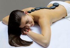 Hot stone therapy. A model having lying on the massage bed and having a hot stone therapy Royalty Free Stock Images