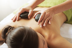 Hot stone therapy. Young woman receiving a hot stone massage therapy at spa Royalty Free Stock Photos