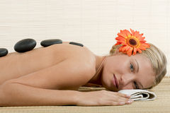 Hot Stone Treatment. Attractive young woman with warm massage stones lined up on her back Royalty Free Stock Images