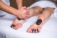 Hot stones lie on the feet of the girl and between the toes. The male hands of the masseur make a foot massage with hot stones Royalty Free Stock Photography