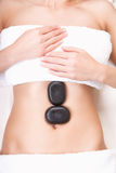 Hot stones on a womans tummy Stock Photo