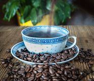 A Hot Stream of Freshly Brewed Coffee Poured into a Cup Made of Chinese Porcelain. Grains of freshly roasted coffee scattered on a rustic wooden board Royalty Free Stock Image