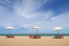 Hot summer beach. Deckchairs and parasol on the white sand beach facing cha-am beach, Thailand Stock Photo