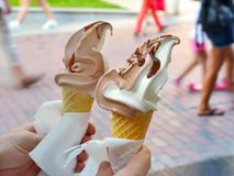 Hot summer day. Men`s hands with two vanilla and chocolate ice creams stock photography