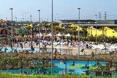Hot summer day with people in water park relax in and at pool royalty free stock image