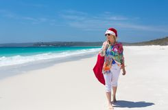 Christmas down on the beach summer sun female walking with santa. Hot summer days Christmas down on the beach or summer vacation southern hemisphere.  A casually Royalty Free Stock Images