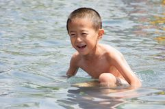 A little boy played happily in the water. In the hot summer, a little boy with no clothes played happily in the water Stock Photo