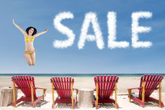 Hot summer sale concept. Summer sale concept with girl jumping over beach chairs Royalty Free Stock Photos