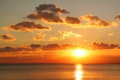 Hot Summer Sunset. Bright sunset on sea with beautiful clouds as wallpaper Stock Photos