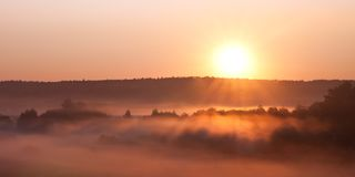 The hot sun rises over the misty valley. Rural morning pastoral landscape stock images