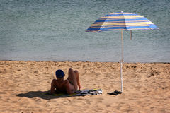 Hot sunny day. Man on the beach under an umbrella Stock Images