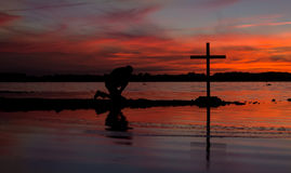 Hot Sunset Lake Prayer Cross. Cross at a lake with a man in prayer beside it, as the sun goes down Stock Photo