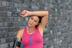 Hot sweaty young woman wiping her forehead. With her arm as she takes a break from jogging through town Royalty Free Stock Image