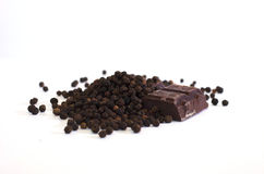Hot and Sweet. Whole black peppercorns and dark chocolate on a white background Royalty Free Stock Photo