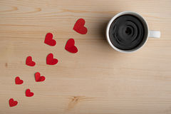 Hot tasty coffee, valentine's day. Path of red hearts on the table, leads to a hot cup of coffee Stock Images