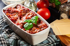 Hot tasty lasagna with spinach in ceramic casserole dish Stock Photography