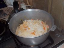 Hot, tasty pilaf in a pig-iron cauldron on a plate royalty free stock images