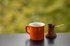 Hot tasty steaming coffee brewed in traditional turkish coffee pot Stock Images