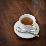 Hot tea. A cup of hot tea with rising smoke is waiting on a wood table Royalty Free Stock Photography