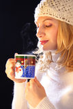 Hot tea. Woman tasting aroma of tea, while cup is still steaming stock images