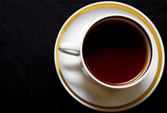 Hot tea. Cup with hot tea on a black background Royalty Free Stock Photography