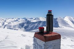 Hot tea adds vigor when hiking in the winter in the mountains. Boundary stone used as a table for a thermos of tea. Hot tea adds vigor when hiking in the winter royalty free stock photos
