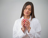 Hot tea and bathrobe lady. Young adult woman holding a hot mug in a bathrobe. Pleasent emotion on face Royalty Free Stock Photos
