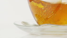 Hot tea being poured into a clear glass cup in slow motion stock video footage