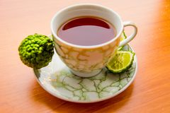 Hot tea with bergamot on wooden table in the cold. Winter royalty free stock photography