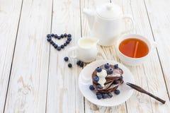 Hot tea and buckwheat chocolate pancakes with blueberries Stock Photo