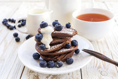 Hot tea and buckwheat chocolate pancakes with blueberries Royalty Free Stock Photography
